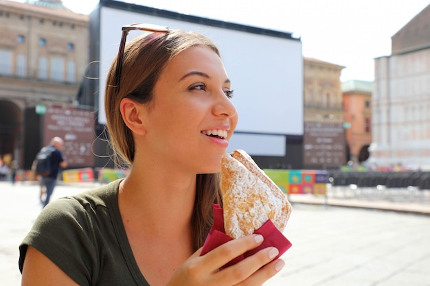 路上のカフェでクロワッサンとコーヒーとイタリアの朝食を持つ若い女性