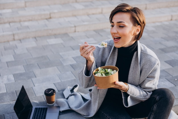 Young woman having lunch and working online