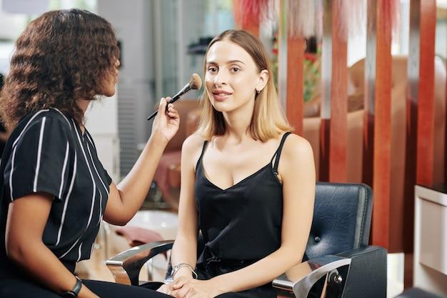 Молодая женщина, делающая макияж