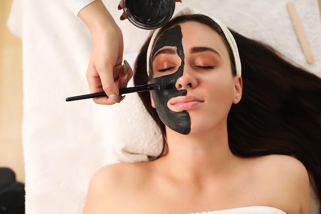 Молодая женщина, имеющая процедуру маски в спа-центре.
