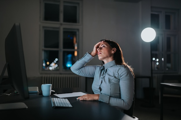 Young woman having a migraine while working overtime.