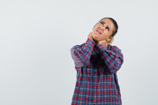 Giovane donna che ha dolore al collo in camicia controllata e sembra esausta, vista frontale.