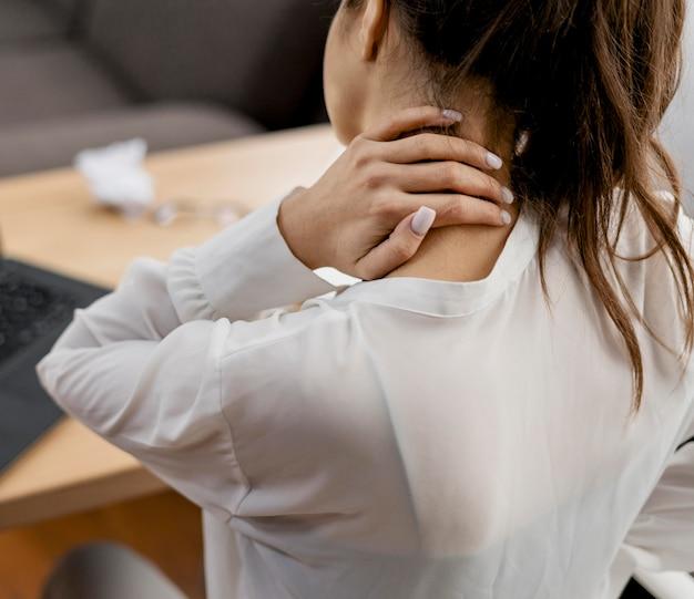 Giovane donna che ha un mal di collo mentre si lavora a casa