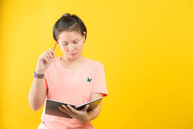 Молодая женщина с блокнотом и карандашом в руках, планирование, экспертиза, анализ, изолированные на желтом фоне, концепция рекламы