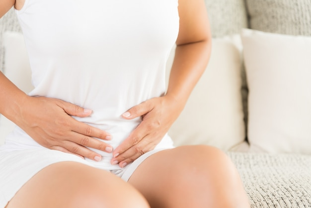 Young woman having painful stomachache sitting on sofa at home. chronic gastritis