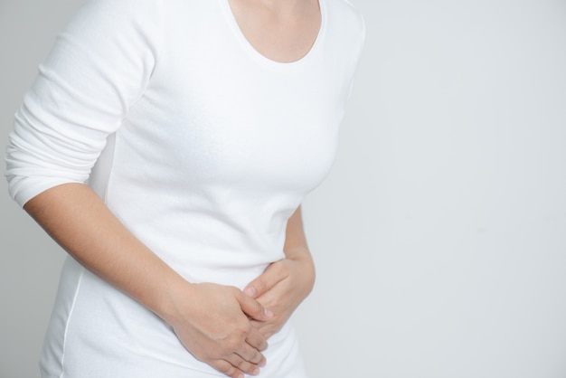 Young woman having painful stomachache on white background