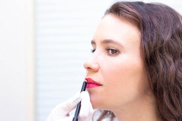 Young woman having permanent makeup on her lips at the beauticians salon.