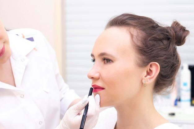 Молодая женщина, имеющая перманентный макияж на губах в салоне косметолога