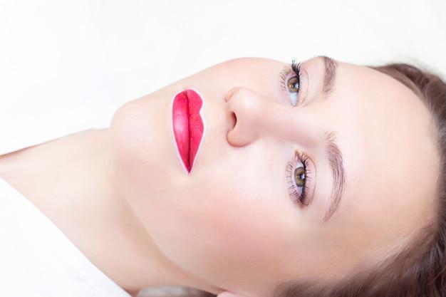 Молодая женщина с перманентным макияжем на губах в салоне косметолога
