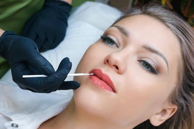 美容院で唇にアートメイクをしている若い女性。唇に液体ガラスを塗る