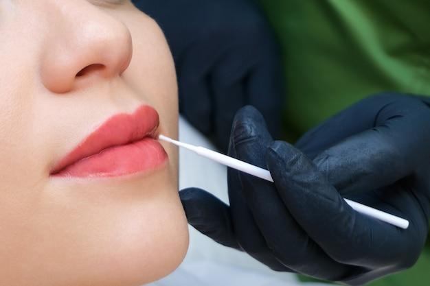 Молодая женщина, имеющая перманентный макияж на губах в салоне косметолога. нанесение жидкого стекла на губы