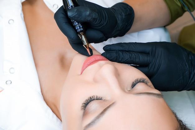Молодая женщина, имеющая перманентный макияж на губах в салоне косметологов. естественный зеленый фон