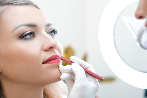 미용실에서 입술에 영구 화장을 하는 젊은 여성. 자연 녹색 배경