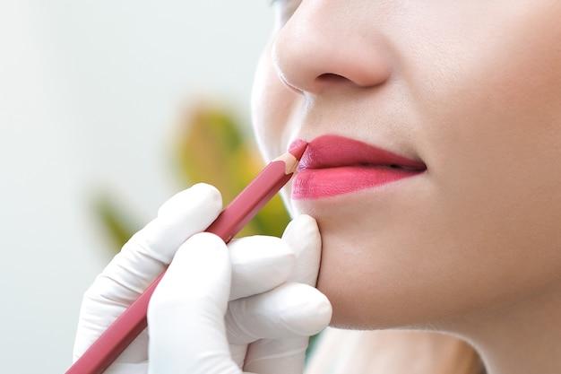美容院で唇にアートメイクをしている若い女性。自然な緑の背景
