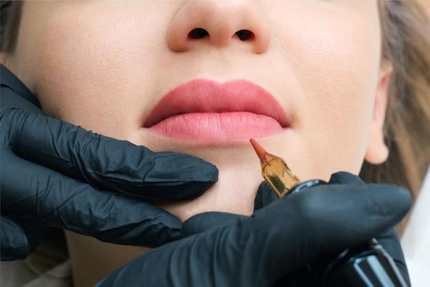 Молодая женщина, имеющая перманентный макияж на губах в салоне косметолога. естественный зеленый фон