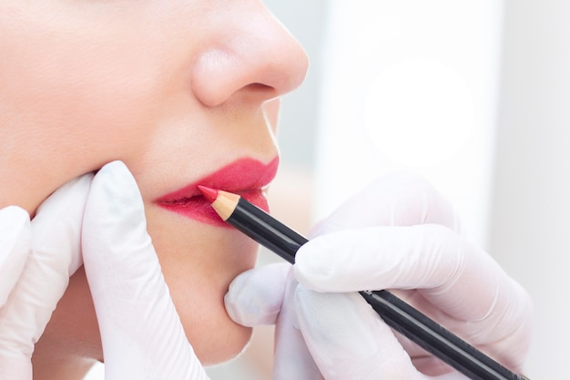 美容師のサロンで彼女の唇に恒久的な化粧を持つ若い女性。アートメイク。白いリップペンシルで輪郭を描く