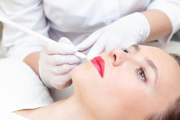 Молодая женщина, имея перманентный макияж на губах в салоне косметологов. перманентный макияж. рисование контура белым карандашом для губ