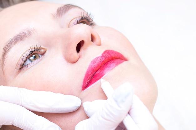 Молодая женщина, имеющая перманентный макияж на губах в салоне косметологов. перманентный макияж (тату). рисование контура белым карандашом для губ
