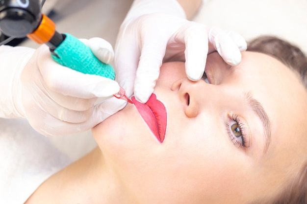 Молодая женщина, имея перманентный макияж на губах в салоне косметологов. перманентный макияж (тату)