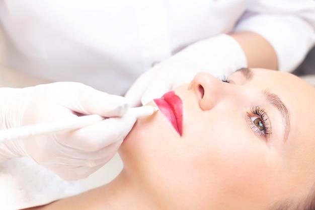 Молодая женщина, имея перманентный макияж на губах в салоне косметологов. перманентный макияж