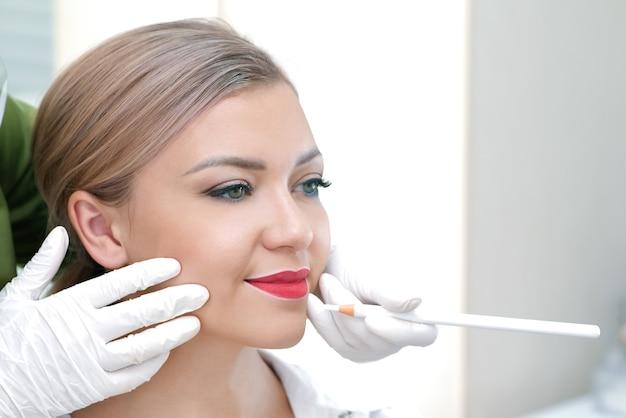 Молодая женщина, имеющая перманентный макияж на губах в салоне косметолога.