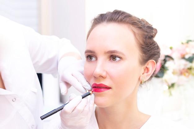 Молодая женщина, имея перманентный макияж на губах