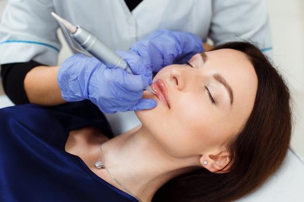 Молодая женщина, имея перманентный макияж на губах в салоне косметолога.