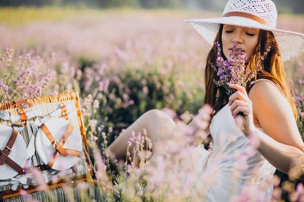 ラベンダー畑でピクニックを持つ若い女性