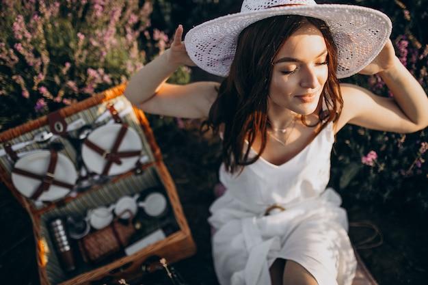 Молодая женщина, пикник в поле лаванды