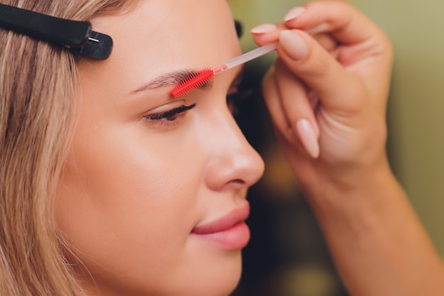 Молодая женщина, имеющая профессиональную процедуру коррекции бровей в салоне красоты.