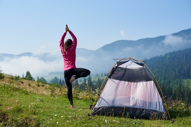 Young woman having a rest near tourist tent in the summer morning in the mountains