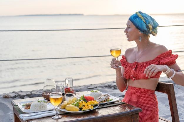 熱帯のビーチで海の波の近くの日没時にホテルのレストランでロマンチックなディナーを持つ若い女性をクローズアップ