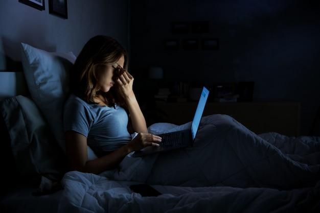 Молодая женщина с болящими и усталыми глазами при использовании ноутбука, сидя в постели ночью