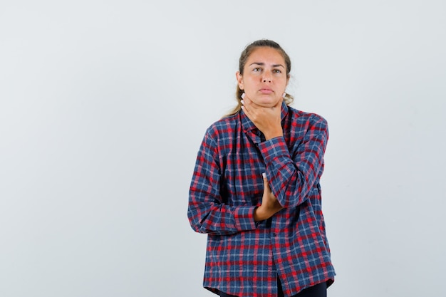 Young woman having sore throat in checked shirt and looking exhausted