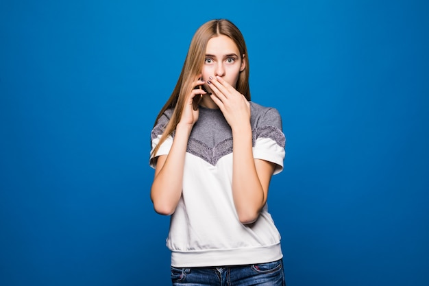 Young woman having a surprised face expression while talking on the telephone