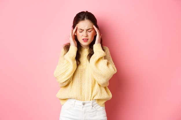 Молодая женщина, страдающая ужасной головной болью, касаясь головы и морщась от боли от мигрени, нуждается в обезболивающих, стоя у розовой стены