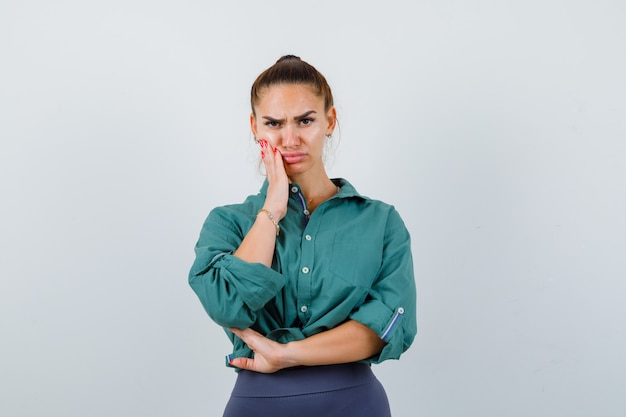 Young woman having terrible toothache in green shirt and looking gloomy. front view.
