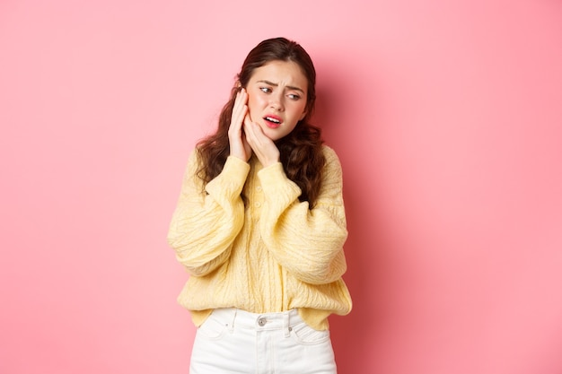 Молодая женщина, страдающая зубной болью, касаясь опухшей щеки и морщась от боли, нуждается в посещении стоматолога, на приеме у стоматолога, стоя у розовой стены