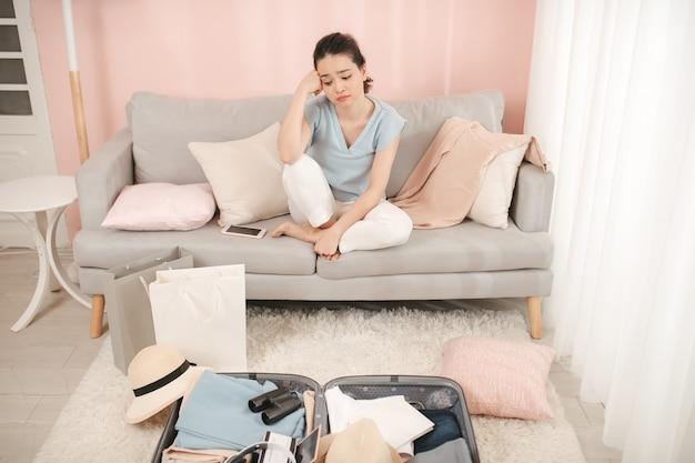 スーツケースのバッグを梱包するのに問題がある若い女性、ソファに座って、関係する顔に手を、準備ができていない、隔離された屋内の部屋の壁