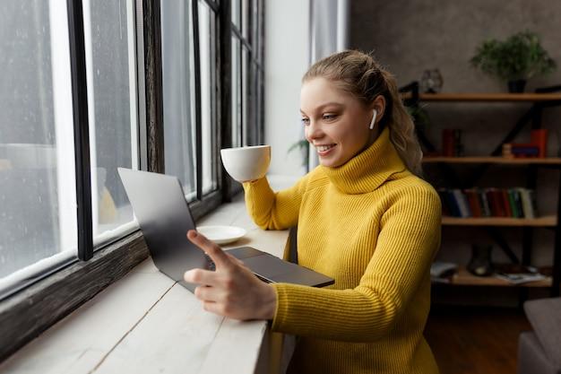 自宅のラップトップコンピューターでビデオ通話をしている若い女性。高品質の写真