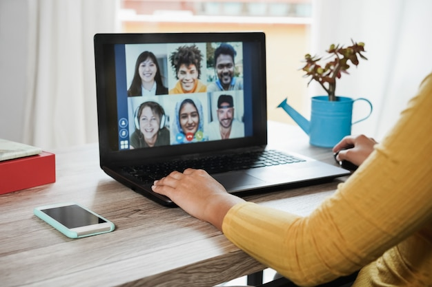 Молодая женщина, имеющая видеозвонок со своими коллегами, используя приложение для портативного компьютера