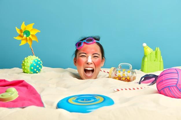 Testa di giovane donna con crema solare sul viso circondato da accessori da spiaggia