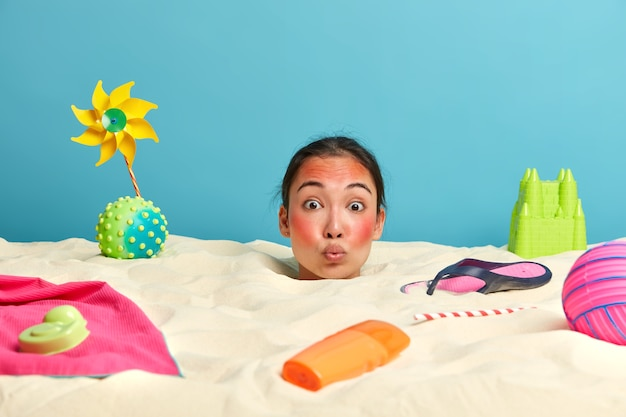 Young woman head with sunscreen cream on face surrounded by beach accessories