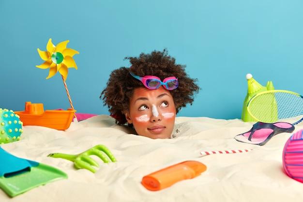 ビーチアクセサリーに囲まれた顔に日焼け止めクリームと若い女性の頭