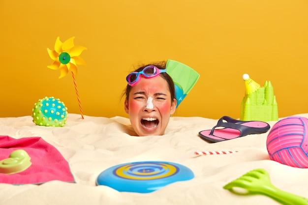 Голова молодой женщины с солнцезащитным кремом на лице в окружении пляжных аксессуаров