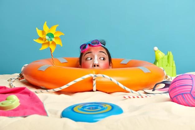 해변 액세서리로 둘러싸인 얼굴에 자외선 차단제 크림과 함께 젊은 여자 머리