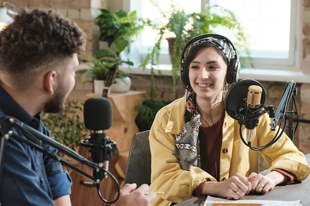 Young woman in headphones giving an interview to young man during broadcasting at radio studio