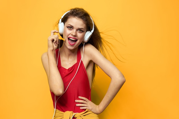 Young woman in headphones having fun and laughing, swimsuit party, yellow