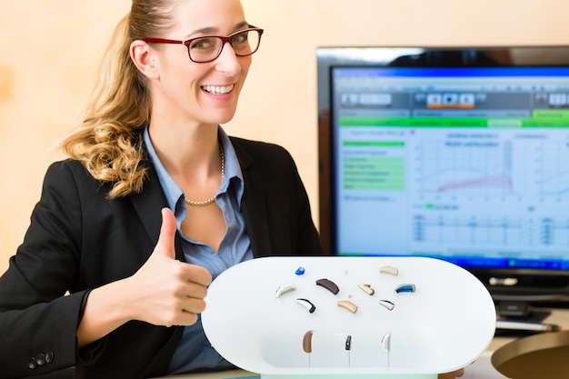 Young woman or hearing accoustician holding a selection of hearing aids