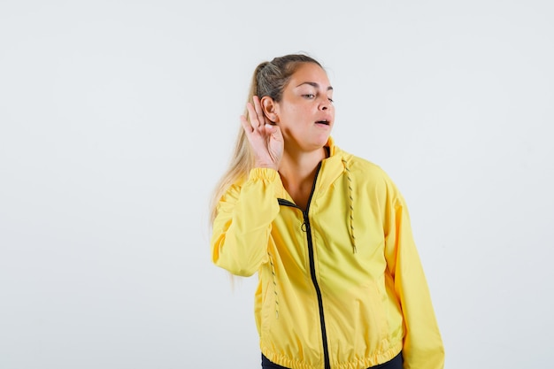 Young woman hearing voices in yellow raincoat and looking careful